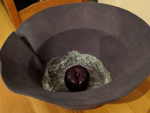 A-Single-Plum-Floating-in-Perfume-Served-in-a-Mans-Hat